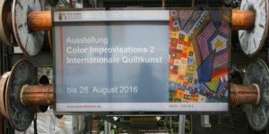 Digital Signage Installation an einem Kettbaumständer Exponat im Fenster des Museums für Tuch und Technik